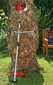 MTD Smart BC52 lutande mot ett träd