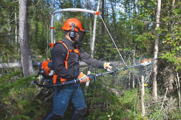 Man som röjer med kedjeröjsåg i skogen